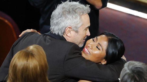 Alfonso Cuaron (kiri) memeluk Yalitza Aparicio, bintang 'Roma' (kanan), saat film itu memenangkan Best Director.