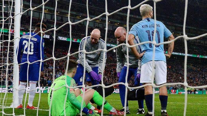 Kepa Rrizabalaga dua kali terduduk di lapangan. Yang kedua dia lakukan sebagai strategi men-delay permainan (REUTERS/Rebecca Naden)