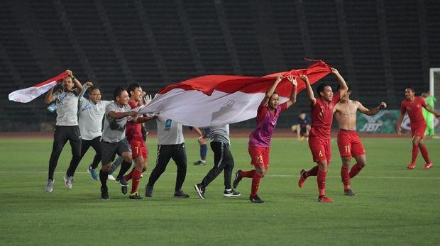 Para pemain dan ofisial meluapkan kegembiraan dengan mengusung bendera Merah Putih di lapangan. (