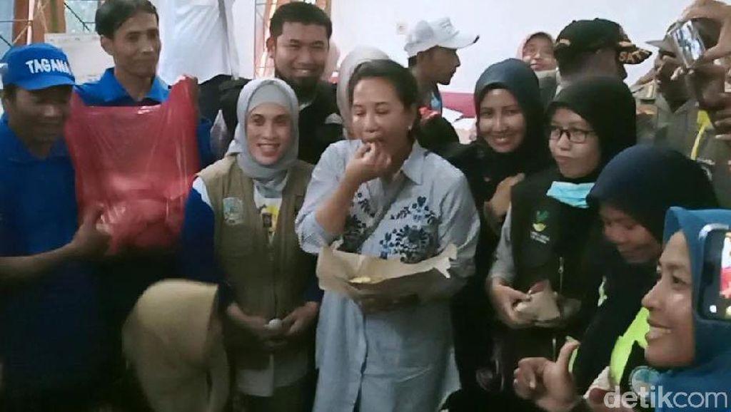 Momen Menteri Rini Cicipi Nasi Bungkus Pengungsi Banjir di Madiun