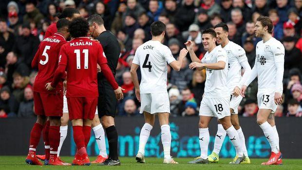 Skuat Burnley berselebrasi ucai cetak gol, sementara pemain Liverpool melakukan protes.