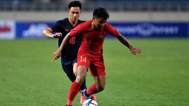 Pesepak bola tim nasional U-23 Indonesia Asnawi Mangkualam (14) berupaya melepaskan diri dari kawalan pesepak bola tim nasional Thailand U-23 Sarachat Supachok (10), pada pertandingan perdana Grup K kualifikasi Piala Asia U-23 AFC 2020, di Stadion Nasional My Dinh, Hanoi, Vietnam, Jumat (22/3/2019). Tim nasional Thailand U-23 mengalahkan tim nasional U-23 Indonesia dengan skor 4-0. ANTARA FOTO/R. Rekotomo/pras.