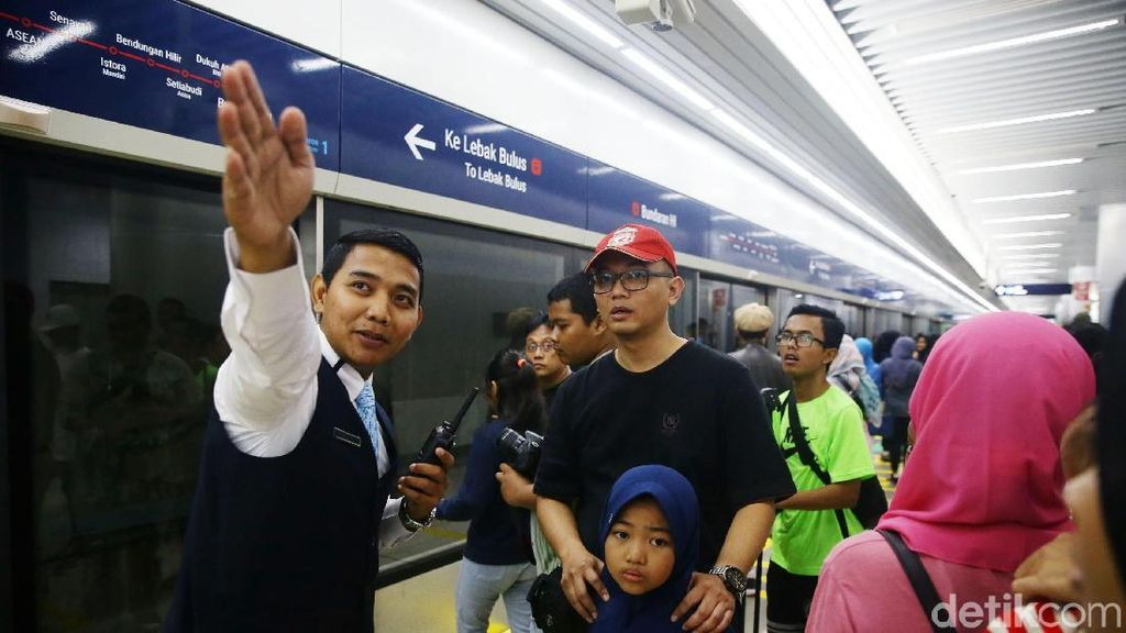 Potret Petugas Bantu Warga yang Antusias Naik MRT