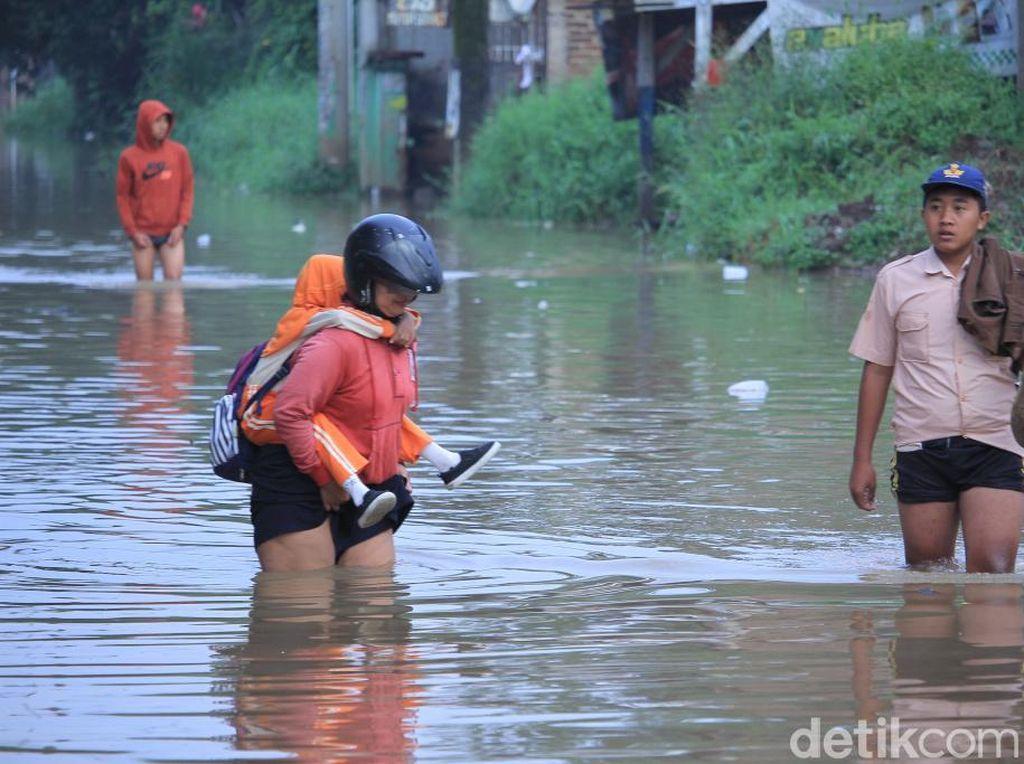 Emak-emak dan Pelajar Terobos Banjir Baleendah Bandung
