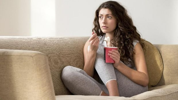 Sad Young woman looking depressed eating ice cream at home