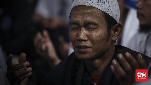 Massa pendukung pasangan capres dan cawapres nomor 02 Prabowo-Sandiaga menangis ketika shalawat usai  sholat berjamaah seblum acara kampanye akbar dimulai di Stadion Utama Glora Bung Karno, Jakarta, 7 April 2019. (CNN Indonesia/ Hesti Rika)