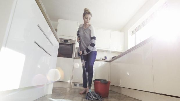 One woman mopping the floor in her kitchen.