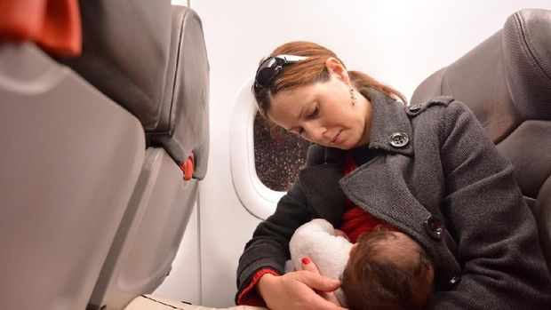 Mother breastfeeding her newborn baby during flight. Concept photo of air travel with baby.