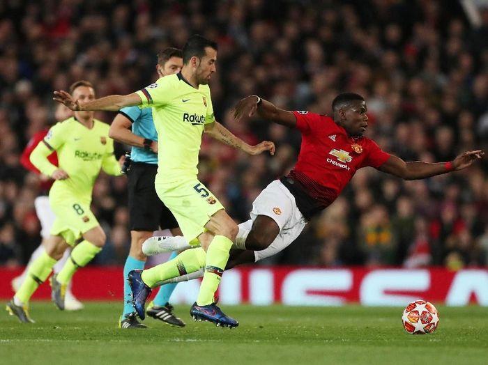 Pemain Barcelona, Sergio Busquets, saat mengadang Paul Pogba di kandang Manchester United. (Foto: Lee Smith/Actions Images via Reuters)