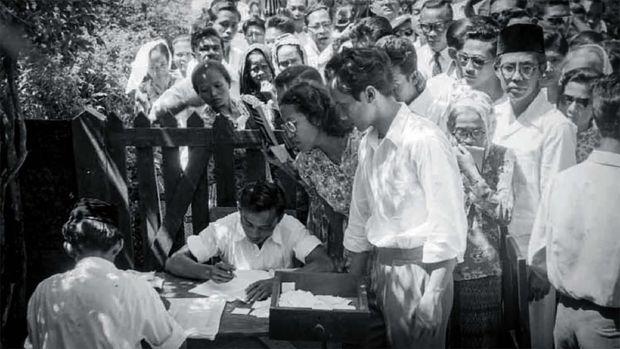 Mohammad Natsir (berkacamata dan memakai peci) Ketua Umum Masyumi, sedang menanti giliran untuk menukar surat suara, 29 September 1955. (Sumber: ANRI)