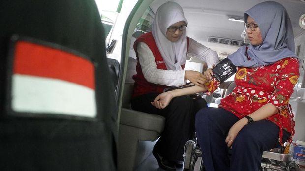 Tenaga medis dari Rumah Sakit Umum Daerah (RSUD) Malang memeriksa tekanan darah petugas penghitung suara saat Rekapitulasi Penghitungan Suara Pemilu 2019 di Panitia Pemilihan Kecamatan (PPK) Kedungkandang, Malang, Jawa Timur, Selasa (23/4/2019). Dinas Kesehatan setempat menyiagakan 30 tenaga medis dan 10 mobil ambulan untuk memberikan layanan kesehatan gratis bagi para petugas penghitung suara yang kelelahan atau sakit saat bertugas. ANTARA FOTO/Ari Bowo Sucipto/hp.