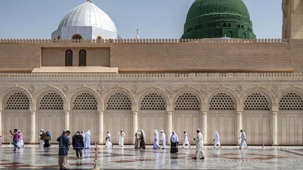 Pengunjung berjalan dengan latar kubah hijau yang menjadi lokasi makam Nabi Muhammad SAW, Abu Bakar as Siddiq, dan Umar bin Kattab di Masjid Nabawi, Madinah, Arab Saudi, Senin (6/5/2019). Ziarah makam Nabi Muhammad SAW dan dua sahabatnya tersebut menjadi salah satu aktivitas favorit Umat Islam saat berkunjung di Kota Madinah Al-Munawarah. ANTARA FOTO/Aji Styawan/foc.