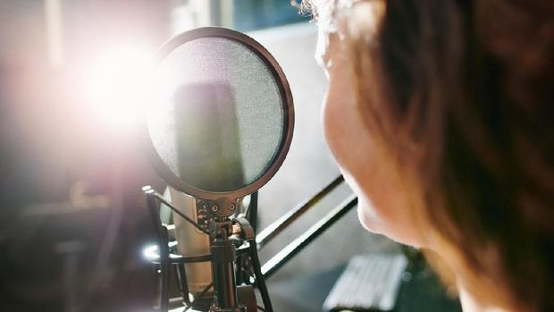 Shot of a woman speaking into a microphone in a recording studio