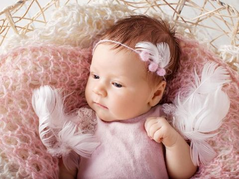 Sweet newborn baby girl with open eyes. Newborn girl 3 weeks old lying in a basket with knitted plaid. Portrait of pretty  newborn girl. Closeup image