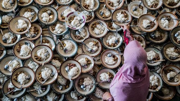 An Indonesian woman prepares meals for Muslims breaking their fast during the holy month of Ramadan at Jogokariyan Mosque in Yogyakarta on May 11, 2019. (Photo by OKA HAMIED / AFP)