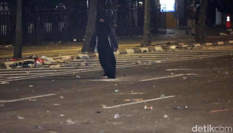 Perempuan Berpakaian Serbahitam dan Membawa Tas Berjalan ke Arah Bawaslu