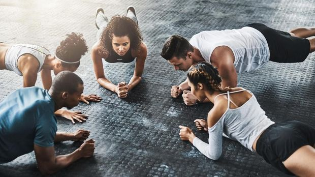 Shot of a group of young people doing planks together during their workout in a gym