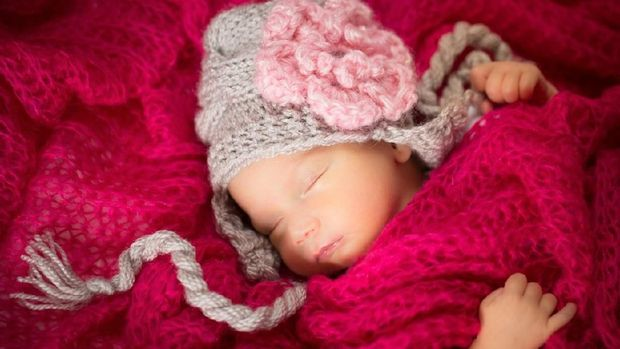 Newborn baby girl wearing a knitted baby hat.