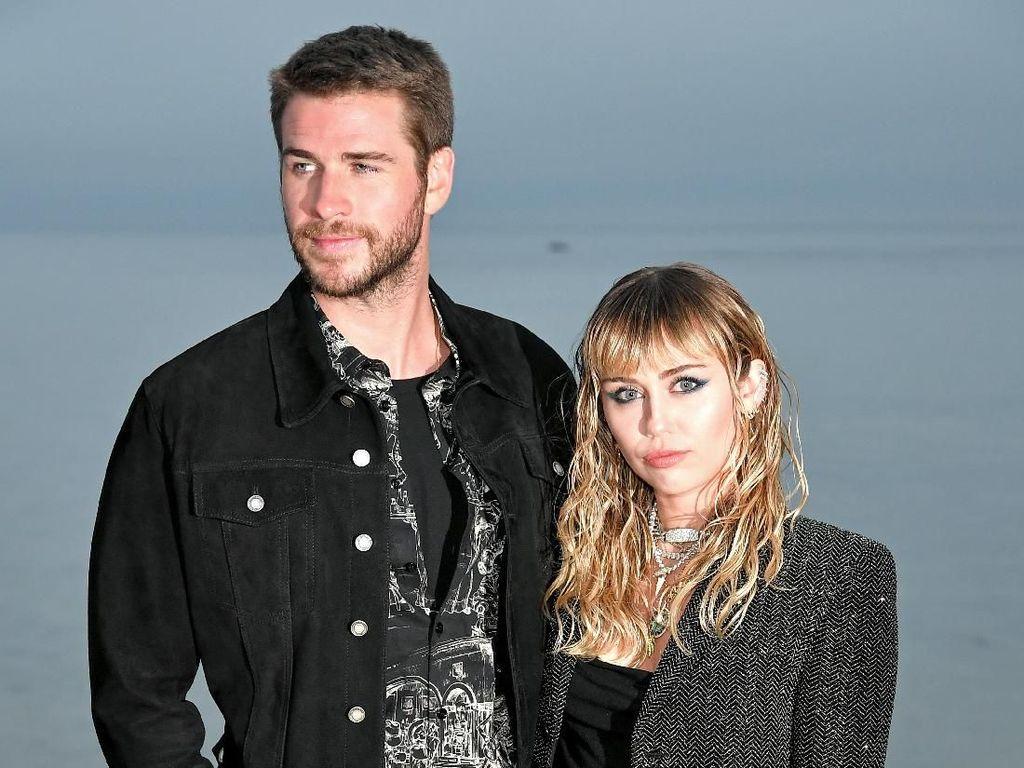 Potret Mesra Miley Cyrus dan Liam Hemsworth di Fashion Show Saint Laurent