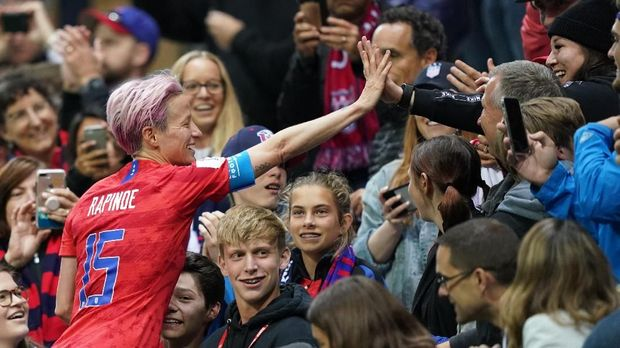 United States' forward Megan Rapinoe (L)  celebrates with supporters after winning  the France 2019 Women's World Cup Group F football match between USA and Thailand, on June 11, 2019, at the Auguste-Delaune Stadium in Reims, eastern France. (Photo by Lionel BONAVENTURE / AFP)