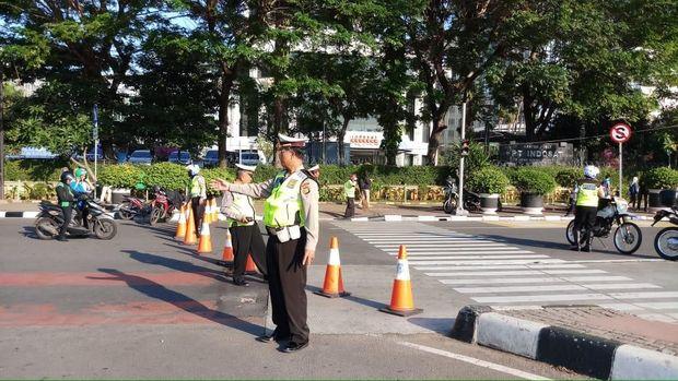 Polisi mengatur arus lalu lintas di sekitar Patung Kuda.