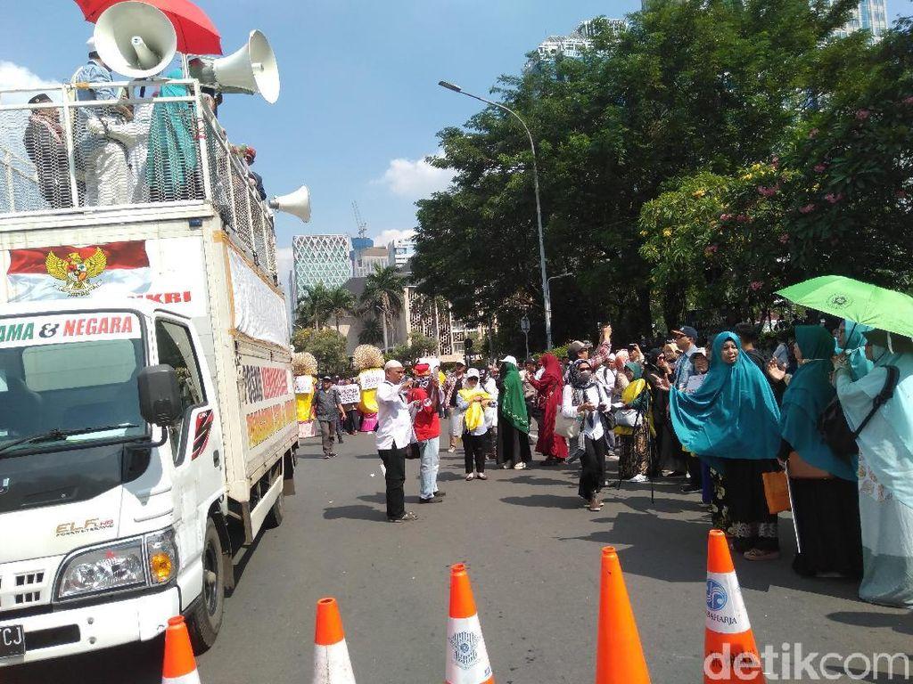 Massa Kawal Sidang MK Bagikan Buku Zikir Bergambar Prabowo-Sandi
