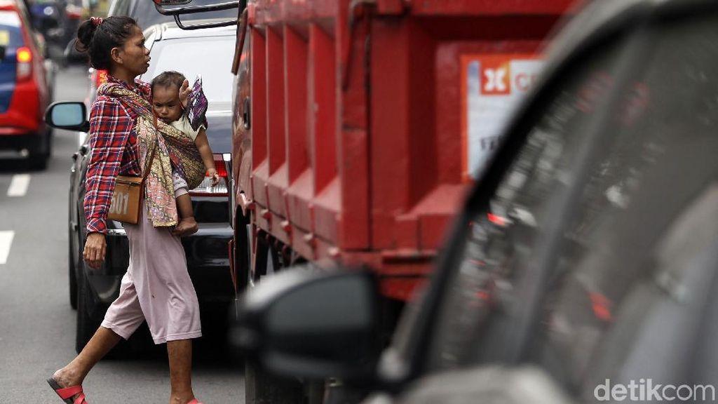 Aksi Pengamen Mencari Uang Sambil Gendong Anak