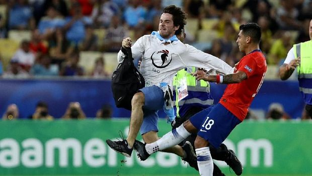 Gonzalo Jara menekel penyusup lapangan.