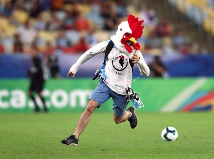 Penyusup bertopeng ayam menerobos lapangan dan menginterupsi laga Chile vs Uruguay di Copa America 2019. (Foto: Ricardo Moraes/Reuters)