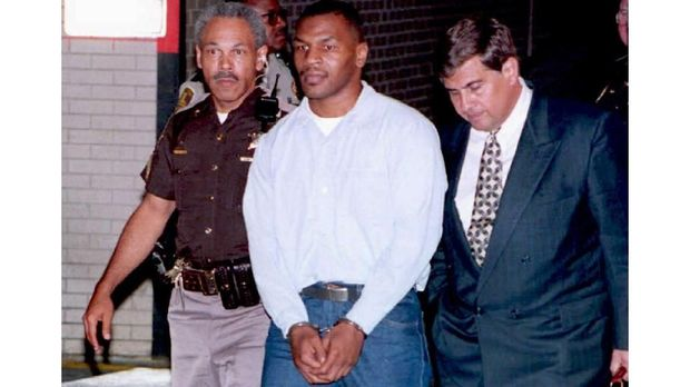 Mike Tyson (C), the former world heavyweight boxing champion, leaves Marion County Courthouse in Indianapolis, Indiana, flanked by his associate attorney Jim Voyles (R) and a police officer (L), after a 13 June 1994 sentence-reduction hearing.  Tyson, who was convicted of rape, is scheduled to be released 25 March. (COLOR KEY: Tyson wears blue trousers.) AFP PHOTO (Photo by EUGENE GARCIA / AFP FILES / AFP)
