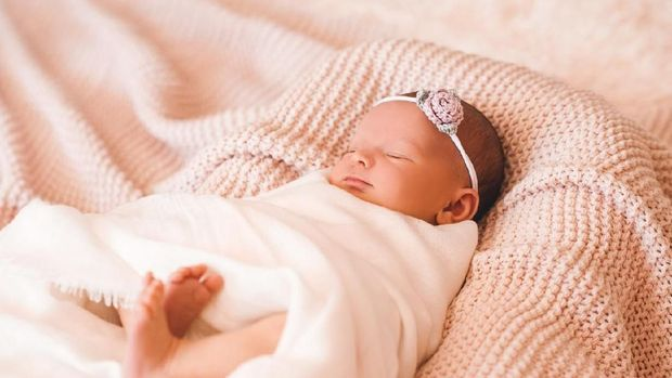 Cute smiling baby girl sleeping in cot closeup. Childhood.