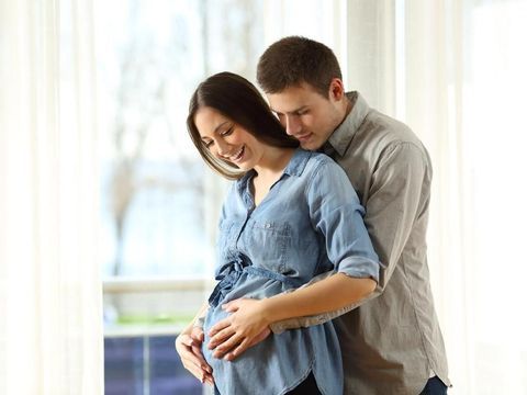 New parents enjoying pregnancy touching belly at home