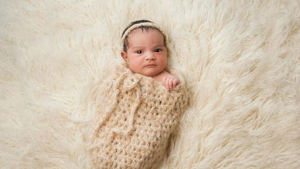 An alert 7 day old, Hispanic baby girl with a displeased look on her face. She is wrapped in a crocheted wool pouch and looking at the camera. Shot in the studio on a cream colored flokati (sheepskin) rug.