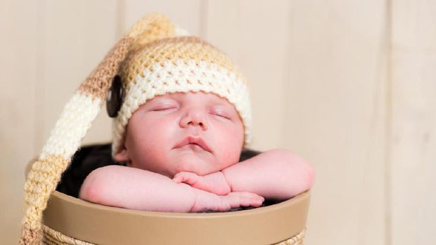 Front view of a cute white Caucasian newborn baby boy sleeping in a decorative basket, hands under the chin holding head, wearing a hand knitted long wool hat. Shot on Canon EOS into a studio. Warm toned edit to emphasize overall softness feel.