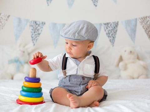 Cute toddler child, baby boy, playing with colorful toy in sunny bedroom, flag banner decoration behind him