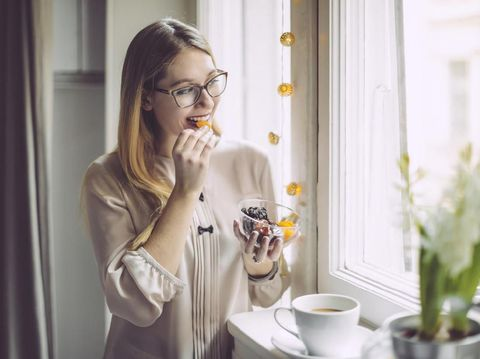 Young woman at home eating dates fruit