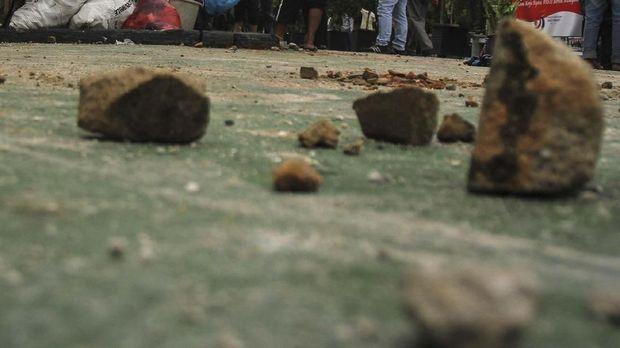 Petugas kebersihan Rutan membersihkan batu dan puing-puing sisa kerusuhan yang berujung pada kaburnya ratusan tahanan di Rutan Sialang Bungkuk Kelas IIB Pekanbaru, Riau, Sabtu (6/5). Akibat kerusuhan pada Jumat (5/5) lalu, dua fasilitas Rutan dan sejumlah mobil rusak serta ratusan tahanan melarikan diri. Hingga saat ini tahanan kabur yang sudah tertangkap sebanyak 212 orang. ANTARA FOTO/Rony Muharrman/aww/17.