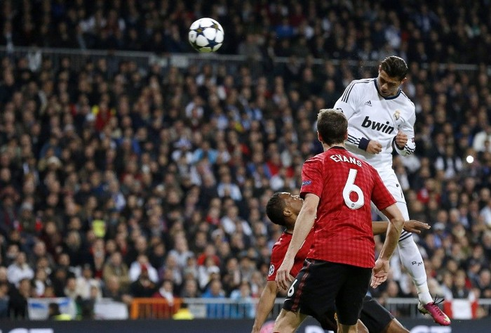 Real Madrid's Portuguese forward Cristiano Ronaldo (top) heads the ball to score during the UEFA Champions League round of 16 first leg football match Real Madrid CF vs Manchester United FC at the Santiago Bernabeu stadium in Madrid on February 13, 2013.  AFP PHOTO / CESAR MANSO (Photo by CESAR MANSO / AFP)