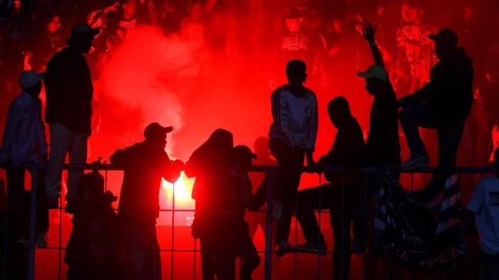 Suporter Arema FC (Aremania) berusaha menghentikan rekannya yang menyalakan cerawat usai pertandingan Liga I antara Arema melawan Persib Bandung di stadion Kanjuruhan, Malang, Jawa Timur, Selasa (30/7/2019). Dalam pertandingan tersebut Arema mengalahkan Persib dengan skor akhir 5-1. ANTARA FOTO/Ari Bowo Sucipto/nz.