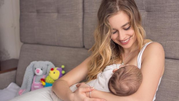 Breastfeeding baby. Pretty mother holding her newborn child. Mom smile and nursing infant. Beautiful woman and new born love at home. Blond mother breast feeding baby.