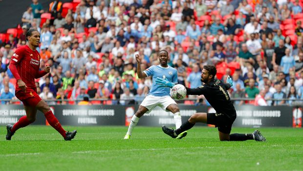 Manchester City's Raheem Sterling takes a shot at goal as Liverpool's goalkeeper Alisson Becker tries a save during the English Community Shield soccer match between Liverpool and Manchester City at Wembley stadium in London, Sunday, Aug. 4, 2019. (AP Photo/Kirsty Wigglesworth)