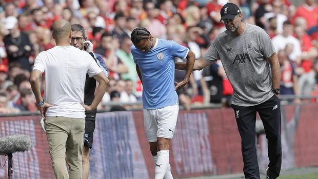 Liverpool's manager Jurgen Klopp, right, pats Manchester City's Leroy Sane as he leaves the pitch after an injury, during the English Community Shield soccer match between Liverpool and Manchester City at Wembley stadium in London, Sunday, Aug. 4, 2019. (AP Photo/Kirsty Wigglesworth)