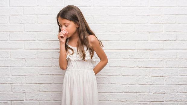 Cute little blond girl coughing in her elbow isolated on white- the technique  recommended by the U.S. Centers for Disease Control and Prevention and the American Academy of Pediatrics.