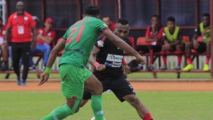 Pemain Persipura Jayapura Titus Bonai (kanan) berebut bola dengan pemain Kalteng Putra Abanda R. (Gusti Tanati/wsj/Antara)