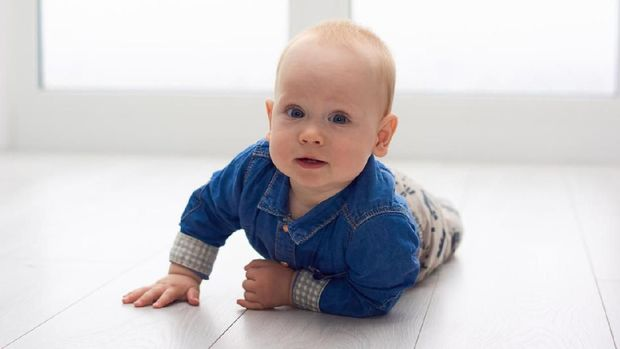 Portrait of a cute little baby in blue denim shirt laying on the floor. Candid image of young baby playing at home