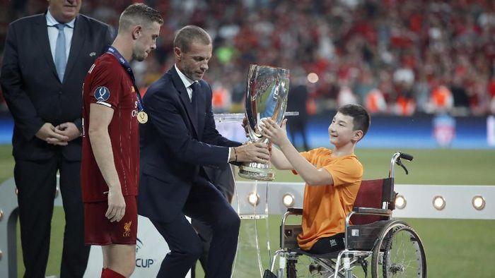 Ali Turganbekov menyerahkan trofi Piala Super Eropa (AP Photo/Thanassis Stavrakis)