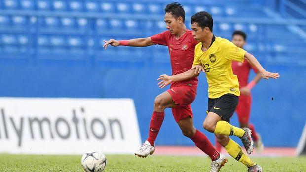 Pesepak bola Indonesia Beckham Putra Nugraha (kiri) berebut bola dengan pesepak bola Malaysia Muhammad Fakrul Iman saat bertanding pada semifinal Piala AFF U-18 di Stadion Go Dau di Provinsi Binh Duong, Vietnam, Sabtu (17/8/2019). ANTARA FOTO/Yusran Uccang/wsj.
