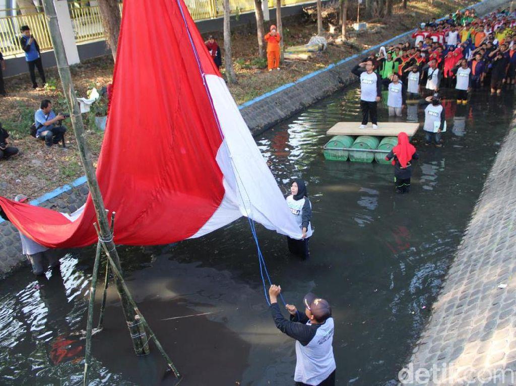 Gelar Upacara di Sungai, Aktivis Lingkungan Kibarkan Bendera Raksasa