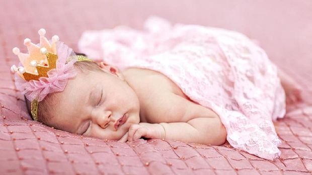 Little baby girl lies on a pink background. Photo session of a newborn baby. Professional newborn photography.