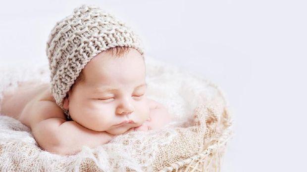 Sweet newborn baby sleeps.  Newborn boy folded handles  in a basket. Copy space